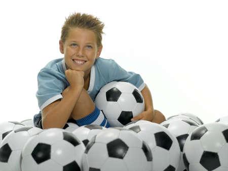 preadolescent: Boy 1013 sitting between footballs LANG_EVOIMAGES