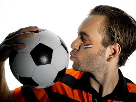 drapeau hollande: Homme avec le drapeau Hollande peint sur la boule baisers de football du visage LANG_EVOIMAGES