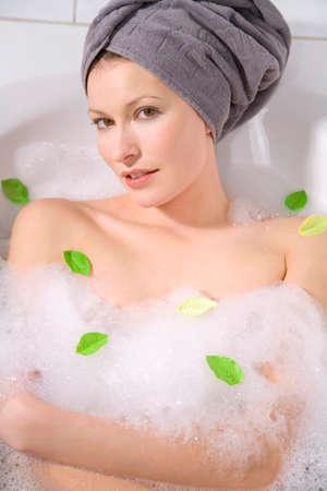 Young woman taking a bubble bath portrait closeup LANG_EVOIMAGES