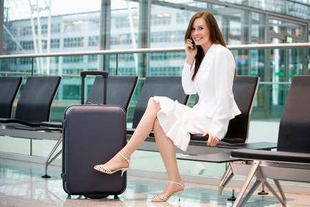 Business-Frau sitzt in Flughafen-Lounge mit Handy lächelnde