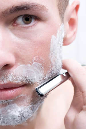 one mid adult man only: Man shaving with razor closeup LANG_EVOIMAGES