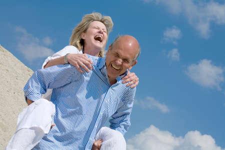 Mature couple man carrying woman piggyback LANG_EVOIMAGES
