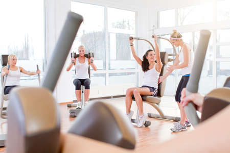 only mid adult women: Germany Brandenburg Instructor with women exercising in gym LANG_EVOIMAGES