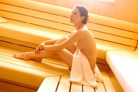 Nackte Frau sitzt in der Sauna Seitenansicht