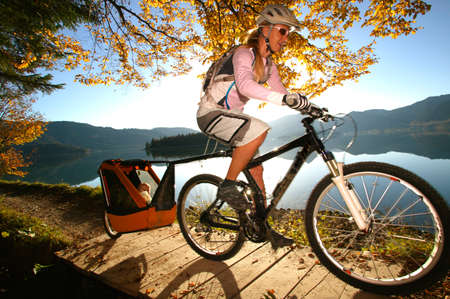 Woman biking at lake with child in trailer