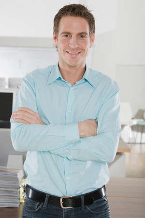 only one mid adult male: Germany Munich young man in office arms crossed smiling portrait closeup LANG_EVOIMAGES