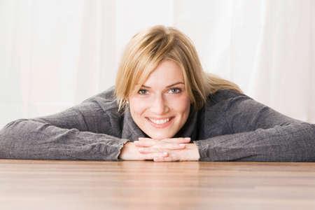 Blonde woman head resting on hands smiling portrait LANG_EVOIMAGES