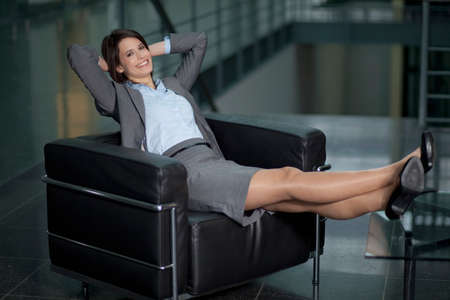 Germany Bavaria Business woman resting on chair smiling portrait