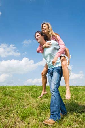 man carrying woman: Man carrying woman piggyback