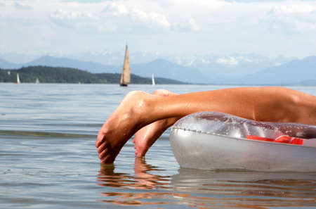 lake front: Woman on air mattress lying on front Lake Starnberg LANG_EVOIMAGES