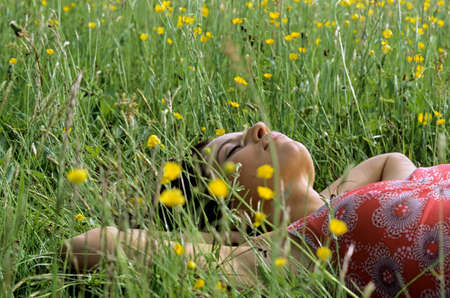 Young woman lying on grass with hands behind head