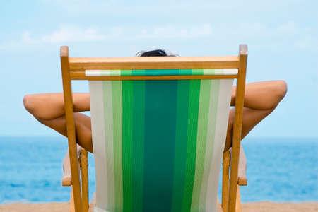 Woman lying in deckchair rear view