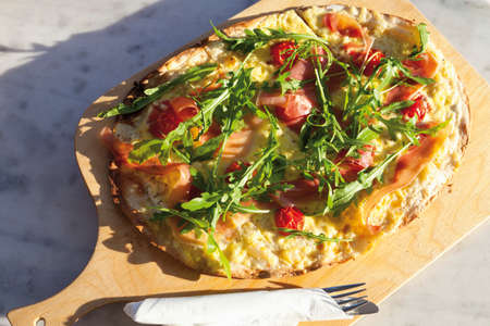 garnished: Tarte flambee garnished with ham rocket and cherry tomatoes
