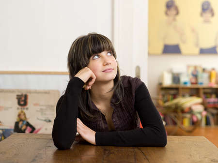 adulthood: Young woman sitting on table thinking