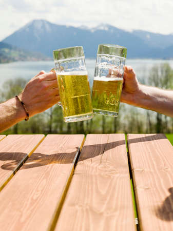 two person only: Germany Bavarian Tegernsee two men toasting with beer glasses closeup
