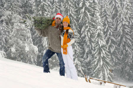 Couple in snow man carrying Christmas tree woman pulling sledge