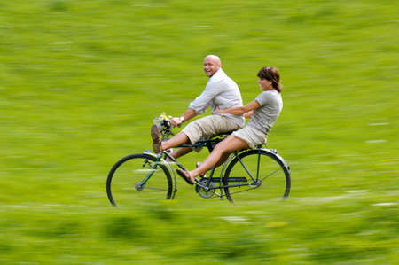 frienship: Couple riding bicycle in meadow side view