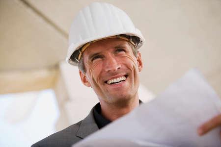 everyday jobs: Man holding blueprint smiling portrait LANG_EVOIMAGES