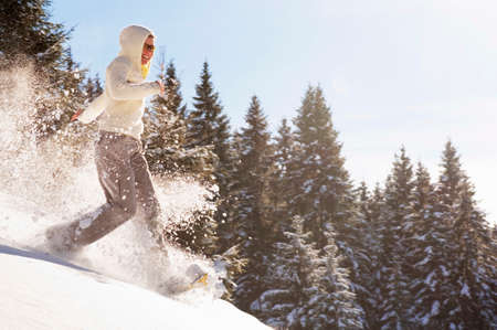 range of motion: Woman snowshoeing in mountains LANG_EVOIMAGES