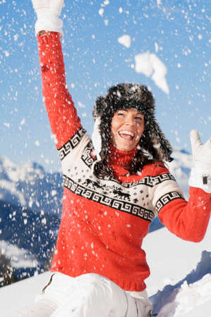 range of motion: Woman in mountains throwing snow
