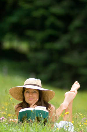 Sommer: Young woman holding book lying in meadow