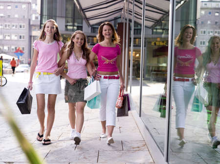 Teenage girls 16-17 years old walking with shopping bags smiling portrait