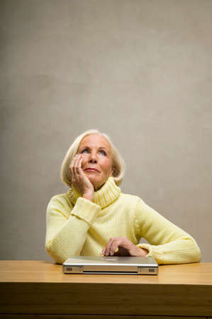 only senior adults: Senior woman sitting with hand on chin in front of laptop on table closeup