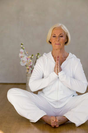 only women: Senior woman with eyes closed in yoga position smiling LANG_EVOIMAGES