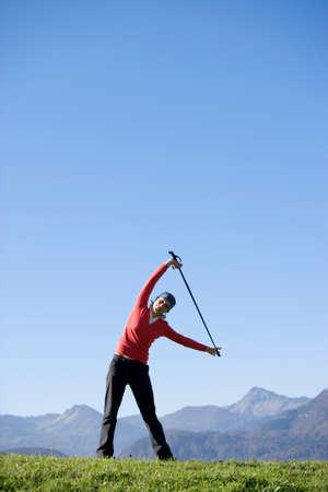 Woman exercising Nordic Walking Austria alps