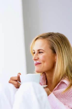 zest for life: Woman holding coffee cup smiling looking away LANG_EVOIMAGES