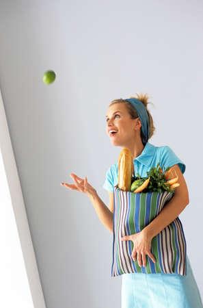 lebensfreude: Frau mit Einkaufstasche Wurf Apfel in der Luft