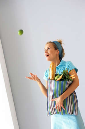 zest for life: Woman with shopping bag throwing apple in air