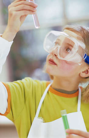 protective goggles: Girl 89 wearing protective goggles with test tube