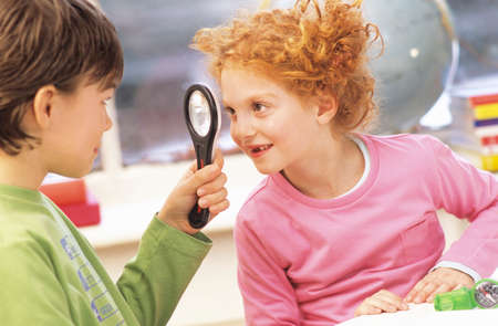 only two people: Boy and girl 79 fooling around with magnifying glass