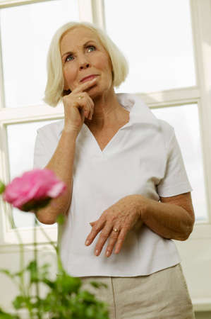 zest for life: Senior woman holding finger on lips looking away portrait