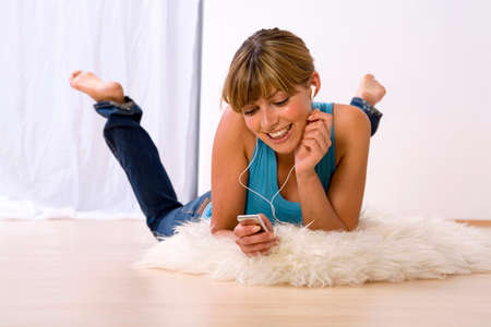 mp3 player: Young woman listening to MP3 player smiling