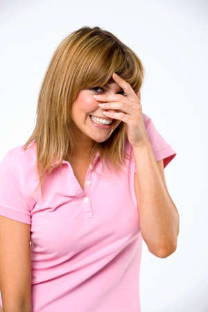 Young woman with hands over face smiling LANG_EVOIMAGES
