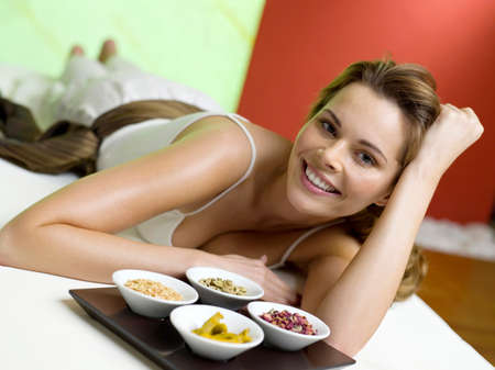 body consciousness: Woman lying on bed with spice in bowls smiling LANG_EVOIMAGES