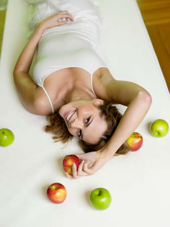 zest for life: Woman lying on bed with apples elevated view