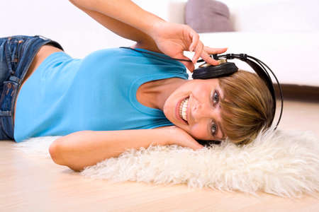 amiable: Young woman lying on floor with headphones smiling