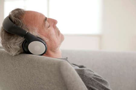 only senior adults: Mature man wearing headphones eyes closed focus on foreground LANG_EVOIMAGES