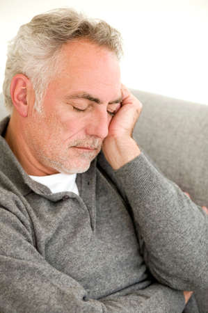 only senior adults: Mature man having nap on sofa elevated view closeup LANG_EVOIMAGES