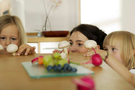 Mother with children 45 in kitchen focus on background