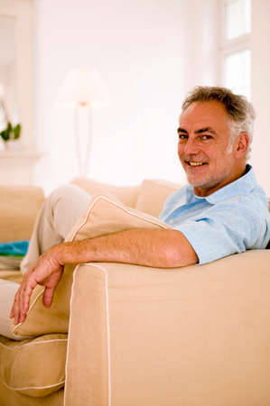only senior adults: Mature man sitting on sofa in living room portrait closeup