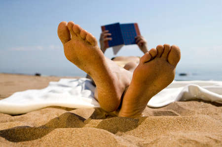 Woman lying on beach reading book focus on foreground
