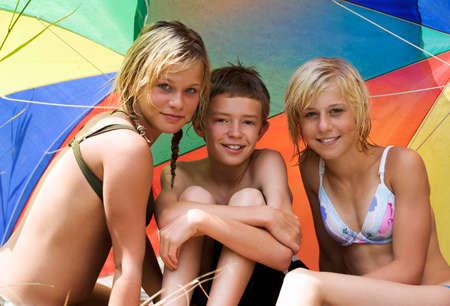 mojado: Muchacho y muchachas que se sientan bajo la sombra del sol