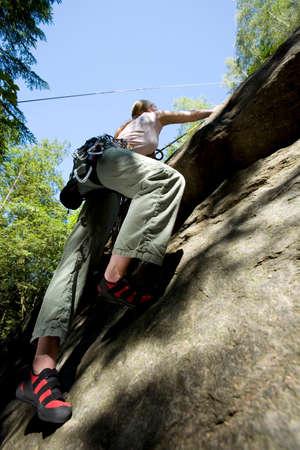 climbing  wall: Young woman mountain climbing in climbing wall