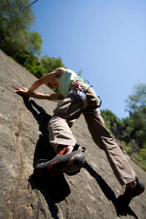Young man rock climbing low angle view