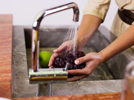 mid section: Woman washing grapes at kitchen sink mid section