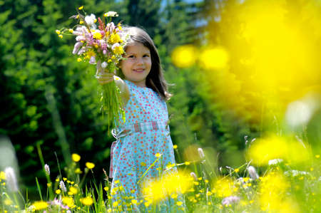 Sommer: Girl 67 holding bunch of flowers in meadow smiling LANG_EVOIMAGES